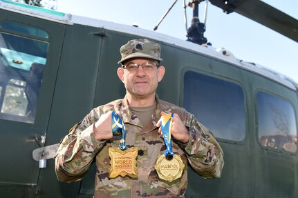 Lt. Col. Pete Caragher, Deputy G-3, 85th U.S. Army Support Command, holds two medals that he won in a Brazilian Jiu-Jitsu competition one is a 2014 World Masters gold medal and the other is a first place gold medal from the 2013 International Brazilian Jiu-Jitsu Federation Championship.