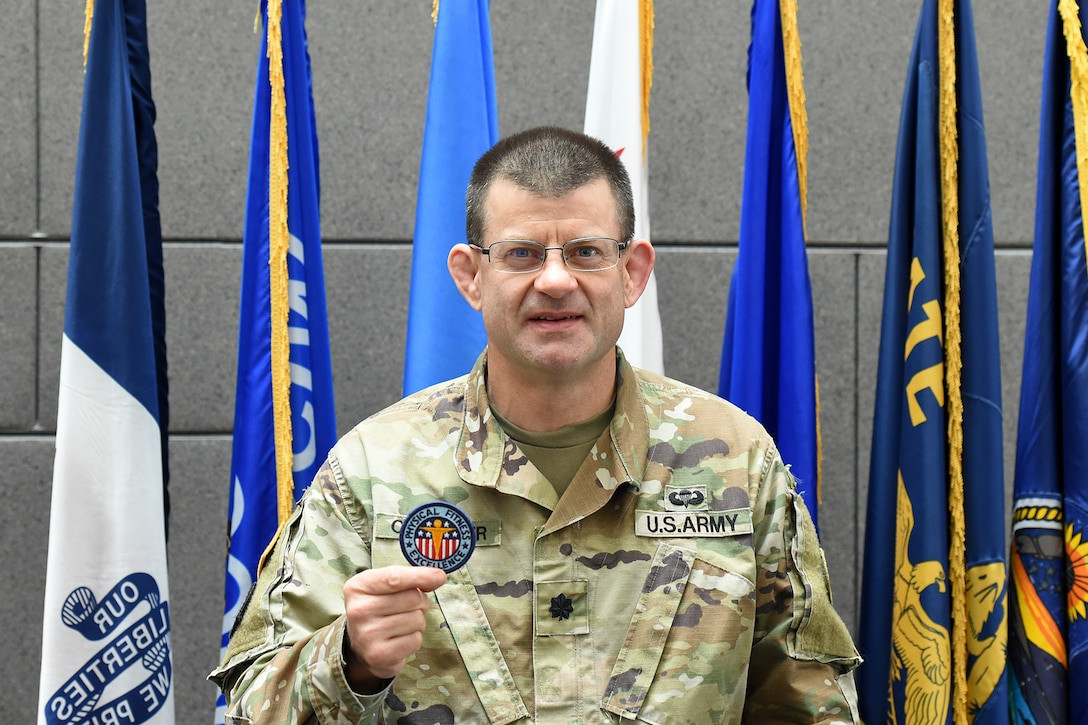 Lt. Col. Caragher, Deputy G-3, 85th U.S. Army Support Command, shows his Army Physical Fitness Badge during a weekend battle assembly, October 20, 2019.