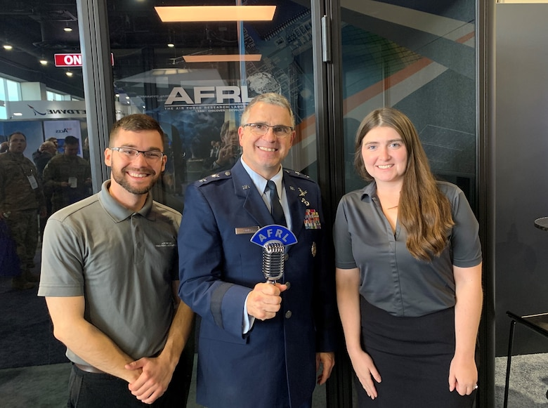 Maj. Gen. William Cooley, commander of the Air Force Research Laboratory, joins AFRL Lab Life podcast co-hosts, Kenneth McNulty and Michele Miller at the Lab Life podcast booth on the floor of the Air Force Association's Air, Space, and Cyber conference exhibit area during the 2019 Air, Space, and Cyber conference. Cooley joined other senior Air Force leaders as guests on the podcast, sharing views on Air Force science and technology growth. (Courtesy photo)