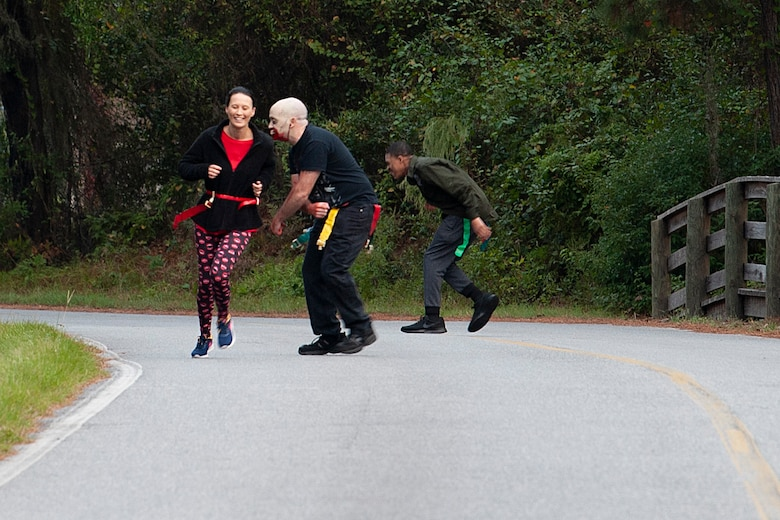 """A Zombie Run volunteer chases a participant Oct. 24, 2019, at Moody Air Force Base, Ga. Participants began the run with two flags on their belts to identify their """"lives."""" Each participant was challenged with running from volunteers dressed as zombies, ensuring participants do not lose a """"life."""" (U.S. Air Force photo by Airman 1st Class Jasmine M. Barnes)"""