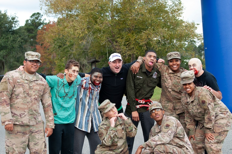"""Zombie Run volunteers and Team Moody Airmen pose for a photo Oct. 24, 2019, at Moody Air Force Base, Ga. Participants began the run with two flags on their belts to identify their """"lives."""" Each participant was challenged with running from volunteers dressed as zombies, ensuring participants do not lose a """"life."""" (U.S. Air Force photo by Airman 1st Class Jasmine M. Barnes)"""