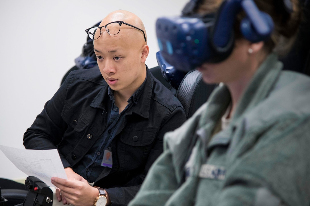 Derrick Ng, NASA aerospace engineer intern, observes a future student of Pilot Training Next version three during a virtual reality flight at Joint Base San Antonio-Randolph, Texas, Oct. 22, 2019, as part of a collaborative research agreement between PTN and NASA. The partnership will focus on biometric data collection and the application of emerging technology into PTN curriculum that will innovate the student pilot learning environment. (U.S. Air Force photo by Sean M. Worrell)