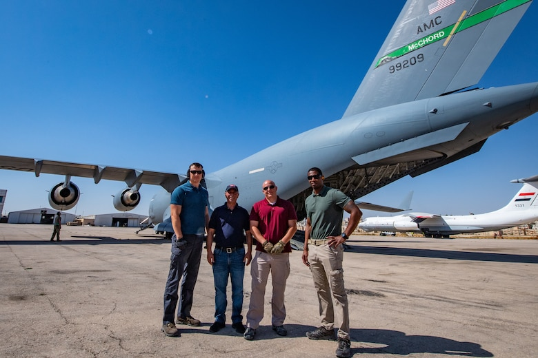 Members of the American Embassy to Jordan, Military Assistance Program, Aerial Logistics Port pose for a picture in front of a U.S. C-17 Globemaster III in Jordan, Oct. 14, 2019. During the team's time in Jordan they have handled over 370 missions, coordinated logistics for 430 tons of cargo, and manifested over 3,000 passengers in support of State Department diplomatic efforts and Department of Defense training missions such as Exercise Eager Lion, U.S. Central Command's largest exercise. Pictured are: Staff Sgt. Tony Bellew, Mr. Akram Al Ramone, Tech. Sgt. Kyle Hersel, and Master Sgt. Chester Moore.