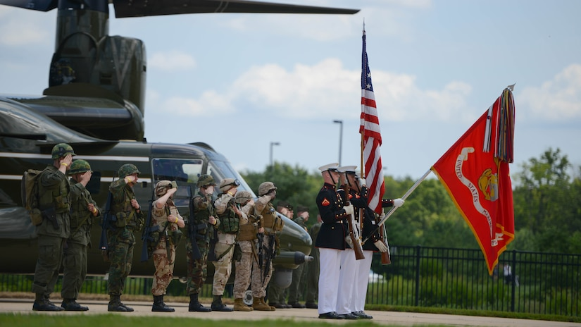Marines in green and khaki uniforms and helmets salute in front of a helicopter and stand behind a Marine color guard with rifles, an American flag and a Marine Corps flag lowered.