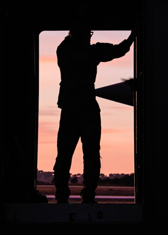 Staff Sgt. Tyler Thomas, a 700th Airlift Squadron loadmaster, surveys the landscape from an open C-130H3 paratroop door during Exercise Real Thaw 2019 at Beja Air Base, Portugal, Oct. 2, 2019. Real Thaw is a Portuguese-led large joint and combined force exercise held annually where Dobbins provided aerial support. (U.S. Air Force photo/Senior Airman Josh Kincaid)