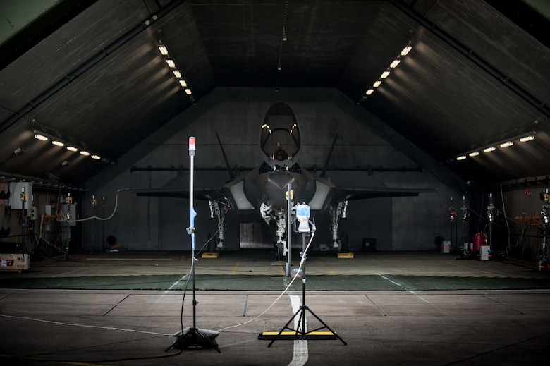 An F-35 is parked inside a hardened aircraft shelter in the Netherlands during an acoustics and air quality testing session, led by experts in the Air Force Research Laboratory's 711th Human Performance Wing. Microphones are attached to the skin of the fighter, to the pilot in the cockpit, and to maintainer areas in front to measure and collect data for an official report. (Photo courtesy of Royal Netherlands Air Force)