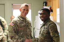 Sgt. Major of the Army Micheal A. Grinston, awards Spc. Khari Johnson, 1st Theater Sustainment Command, a coin of excellence for maintaining high standards, during his visit to Fort Knox, Ky.