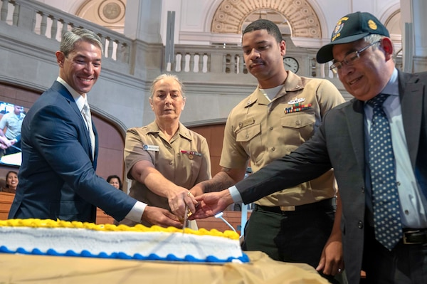 """(From left) San Antonio Mayor Ron Nirenberg; Capt. Elizabeth Montcalm-Smith, Navy Medicine Education, Training and Logistics Command acting deputy commander; Petty Officer 2nd Class Lebron Freeman, assigned to Navy Medicine Training Support Center; and Navy Veteran Any Segovia, San Antonio city attorney, cut the 244th Navy birthday cake during a city hall meeting. The city recognition included the Navy birthday cake cutting, singing """"Anchors Aweigh"""" and honoring Navy active, Reserve and veterans attending."""
