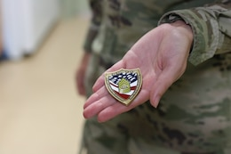 Spc. Kinsley Adams, 1st Theater Sustainment Command, holds a coin she received from Sgt. Major of the Army Micheal A. Grinston, during his visit to Fort Knox, Ky. Oct 23, 2019.
