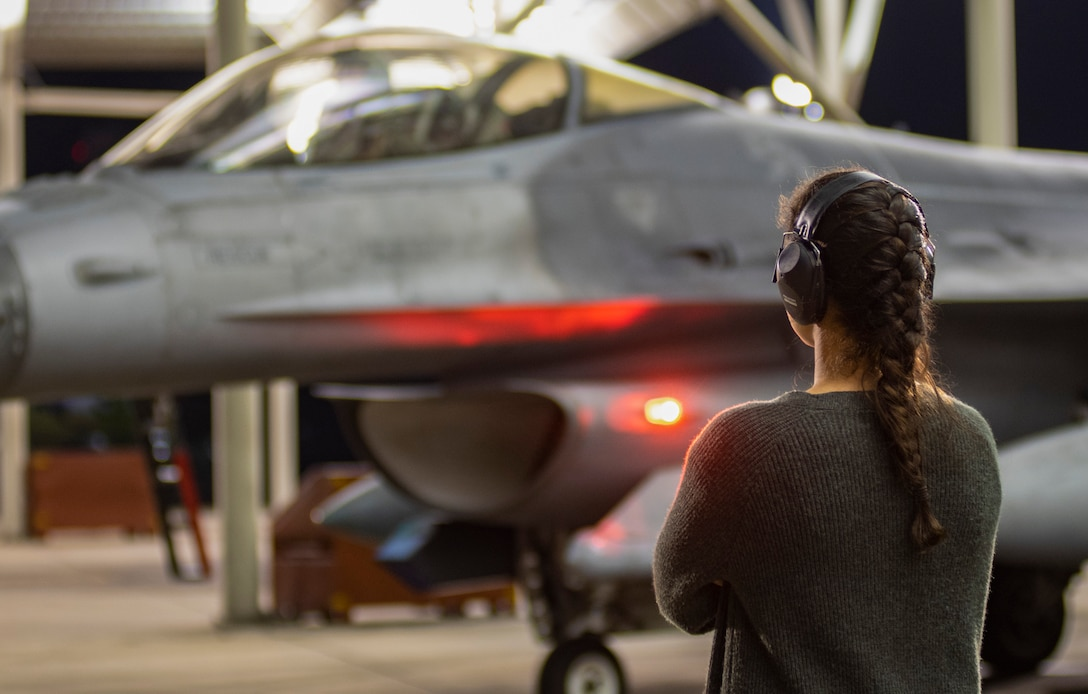 A pilot's spouse watches an F-16CM Viper pilot assigned to the 79th Fighter Squadron prepare for takeoff at Shaw Air Force Base, South Carolina, Oct. 21, 2019.