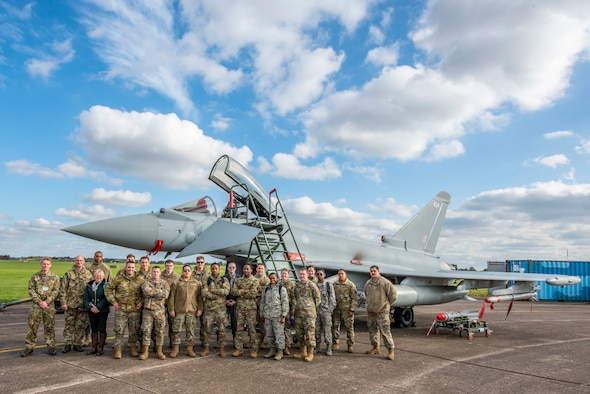 Team Mildenhall Airmen pose for a group photo in front of a Royal Air Force Typhoon FGR.Mk 4 aircraft at RAF Waddington, England, Oct. 22, 2019. The Airmen attended briefings and toured static aircraft displays during the RAF Air Combat Power visit. (U.S. Air Force photo by Airman 1st Class Joseph Barron).