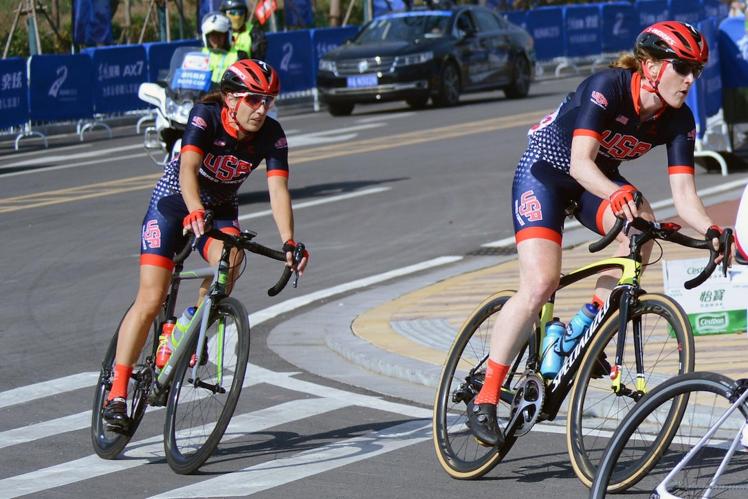 Two cyclists round a corner.