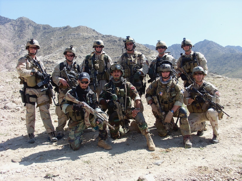 A group of soldiers dressed in full battle uniform pose together on the top of a mountain.