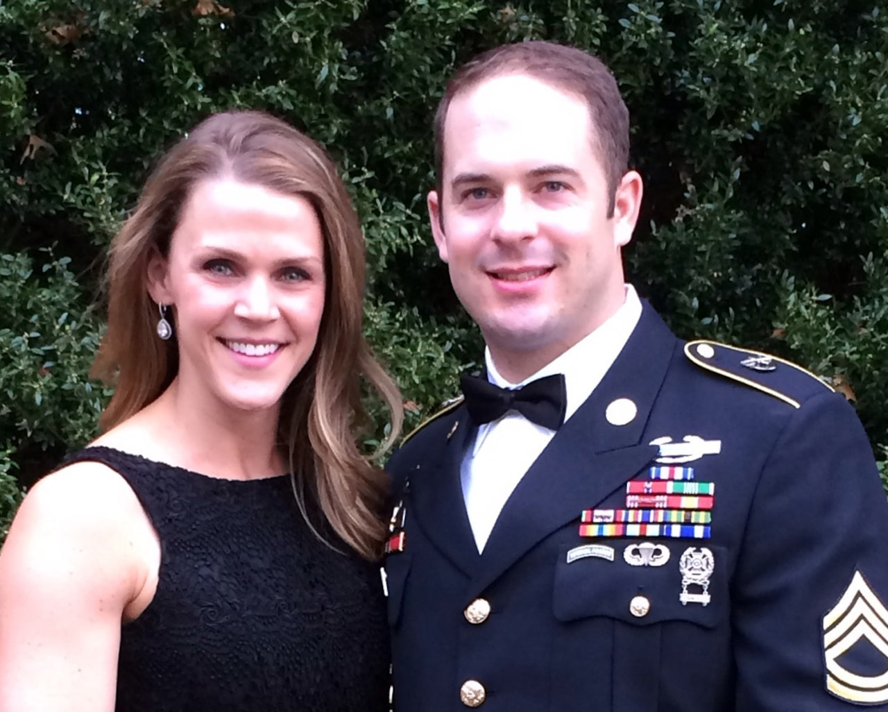 A woman poses with a soldier wearing his dress uniform and bowtie.
