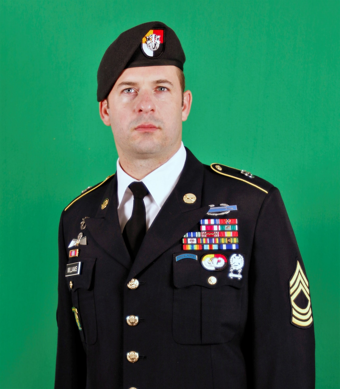 Man wearing dress uniform and beret for an official photo.