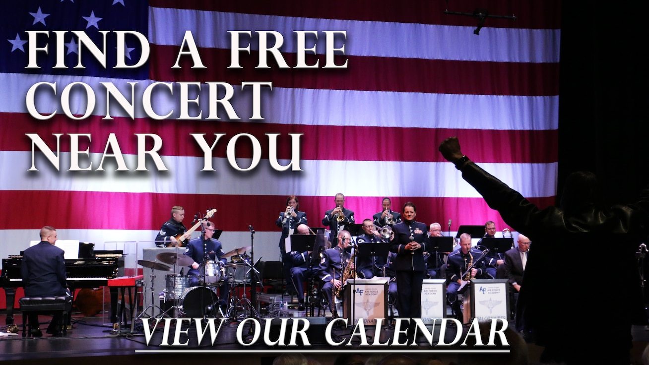 The Falconaires jazz band performs in front of a huge American flag in their blue tunic uniforms as a veteran in the audience stands to be recognized for his service and raises his arms over his head in a proud V.
