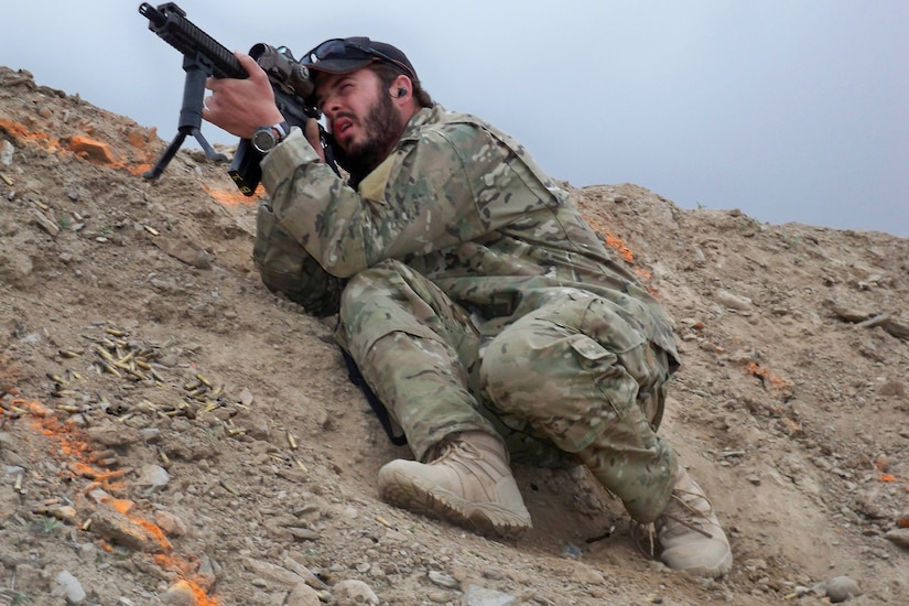 A soldier crouches on the side of a steep dirt mountain looking through the scope of his rifle