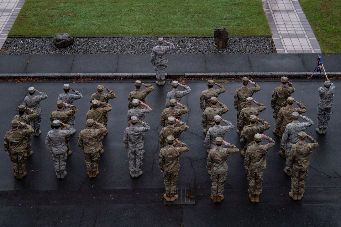 Airmen salute during a retreat ceremony
