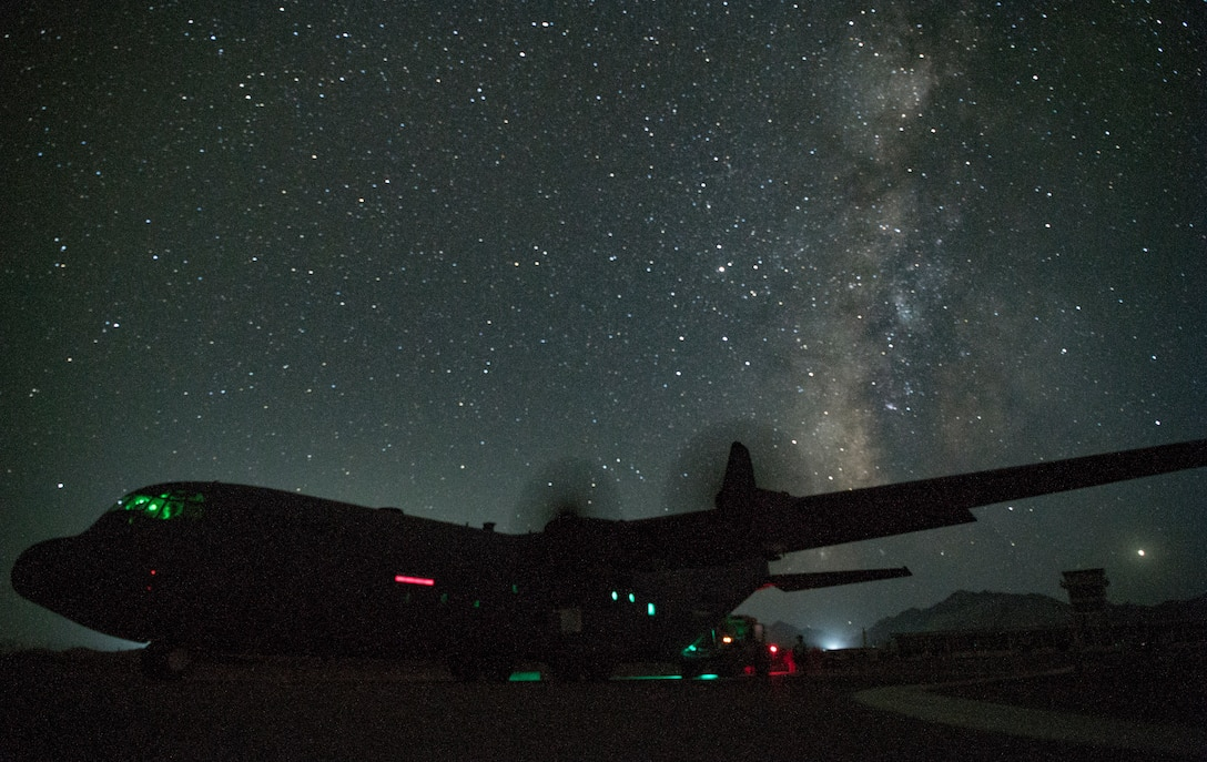 Tactical aircraft sits on a runway against the backdrop of a starry sky.