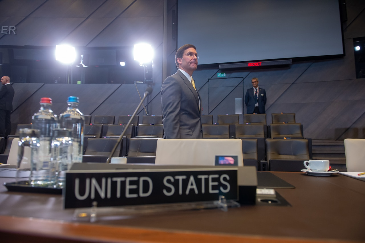 Mark Esper walks in front of bright camera lights, a United States desktop sign in the foreground.