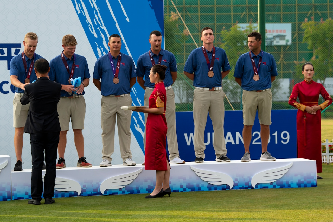Six men receive bronze medals during a presentation ceremony.