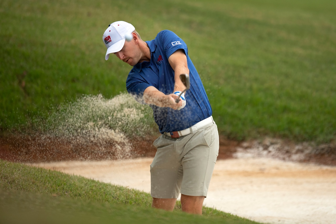 Sand sprays as a golfer hits out of a bunker.