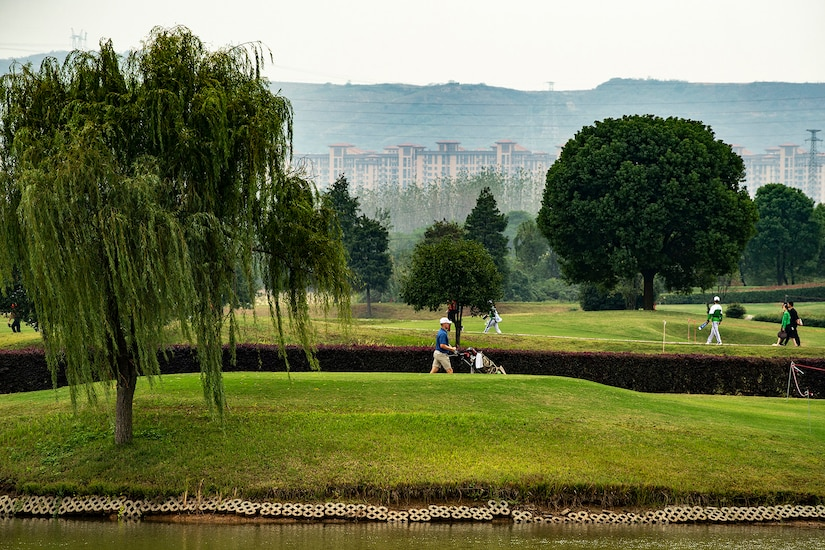 A golfer wheels his clubs next to a green, surrounded by the course's scenic beauty, with trees on the course and mountains in the distance.
