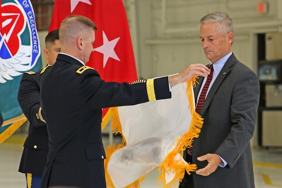 Maj. Gen. Todd Royar, commanding general of the of the U.S. Army Aviation and Missile Command, presents the Senior Executive Service flag to Geoff Downer, director of the AMCOM's Special Programs (Aviation), during a SES appointment ceremony Oct. 18 at Joint Base Langley-Eustis, Virginia.