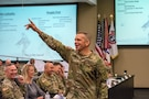 man in army uniform points up in the air.