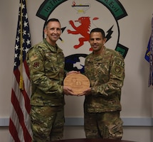 Col. Michael C. Mentavlos, right, the Individual Mobilization Augmentee to the AFOSI Region 6 Commander, was recently selected to represent the Air Force Reserve and AFOSI on the Defense and Security Issues Committee (DEFSEC). Here, Senior Master Sgt. Alan Frank presents him with a token of appreciation from the men and women of the 24th Expeditionary Field Investigations Squadron at the 24 EFIS Change of Command ceremony at Al Udeid Air Base, Qatar, Aug. 15, 2019. (U.S. Air Force photo by Staff Sgt. Ashley L. Gardener)
