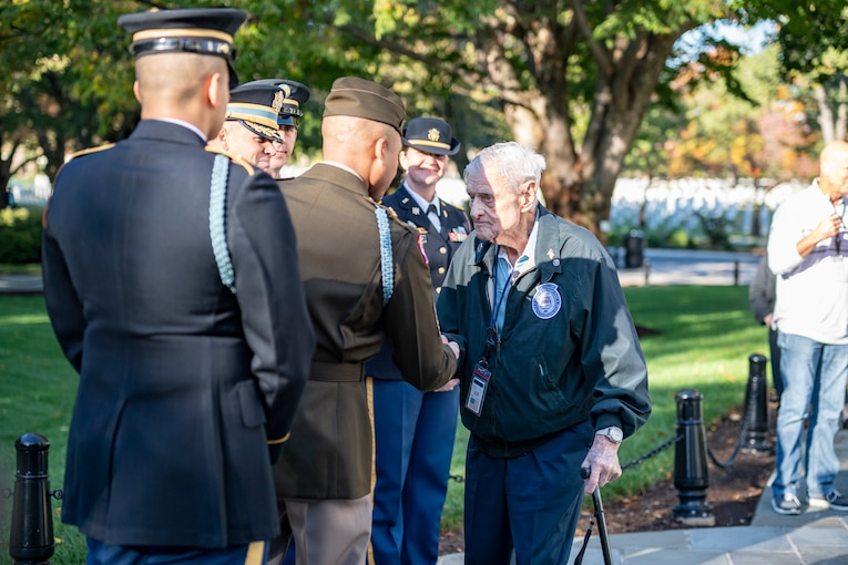 A veteran exchanges greetings with service members at a cemetery.