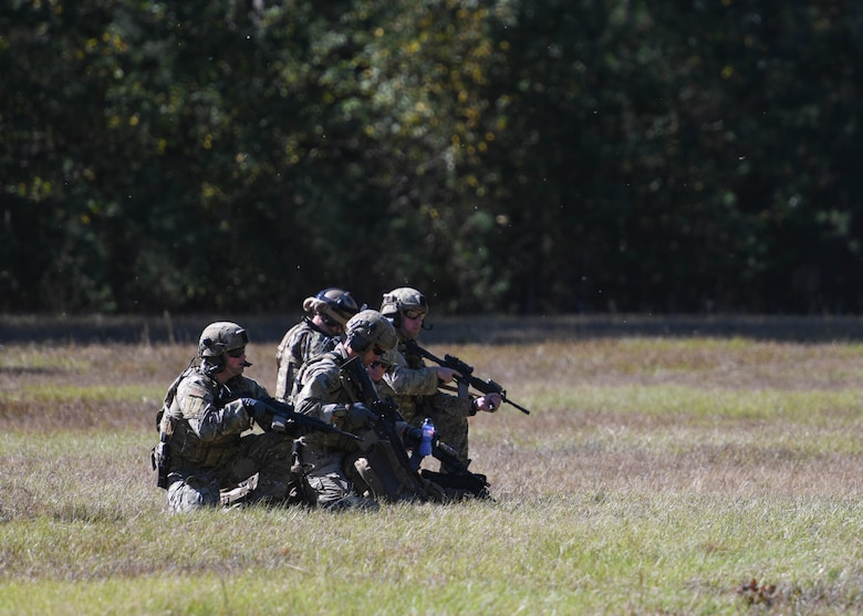 Airman kneel on a grass field holding M4's