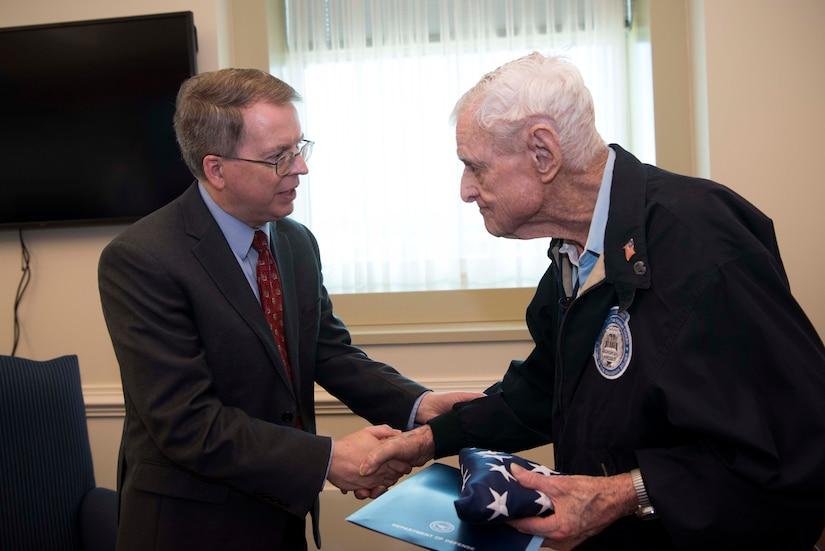 Deputy Defense Secretary David L. Norquist shakes hands with an elderly man
