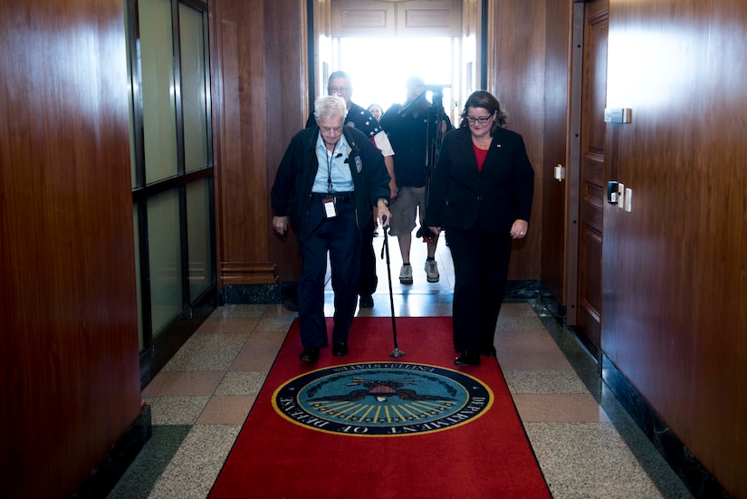 A man and a woman walk through a hallway.