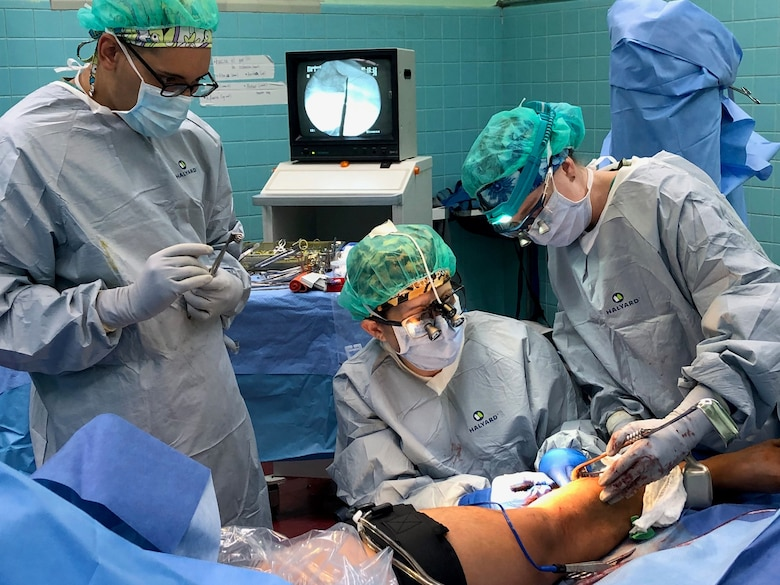 (From Left) Army Spc. Abdiel Santos-Soto, Air Force Maj. Julia Nuelle and Air Force Capt. Tayt Ellison harvest bone to perform a fibular bone graft Sept. 19 during a Medical Readiness Exercise in Tegucigalpa, Honduras. A team of 19 military medical personnel from Brooke Army Medical Center and other military treatment facilities completed 128 procedures from Sept. 14-27.
