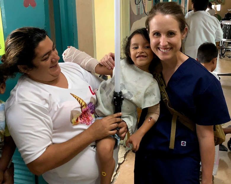 Air Force Maj. Julia Nuelle, chief of Orthopaedic Hand and Microvascular Surgery at Brooke Army Medical Center, poses for a photo with a pediatric patient and her mother Sept. 26 during a Medical Readiness Exercise in Tegucigalpa, Honduras. The team finished their mission by visiting their patients and delivering toys and coloring books to the hospital's pediatric ward. A team of 19 military medical personnel from Brooke Army Medical Center and other military treatment facilities completed 128 procedures from Sept. 14-27.