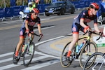 Navy Cmdr. Kathleen Giles and Air Force Lt. Col. Melissa Tallent round the first corner in the second lap of the 50-mile cycle road race in the CISM Military World Games in Wuhan, China, Oct. 20, 2019.