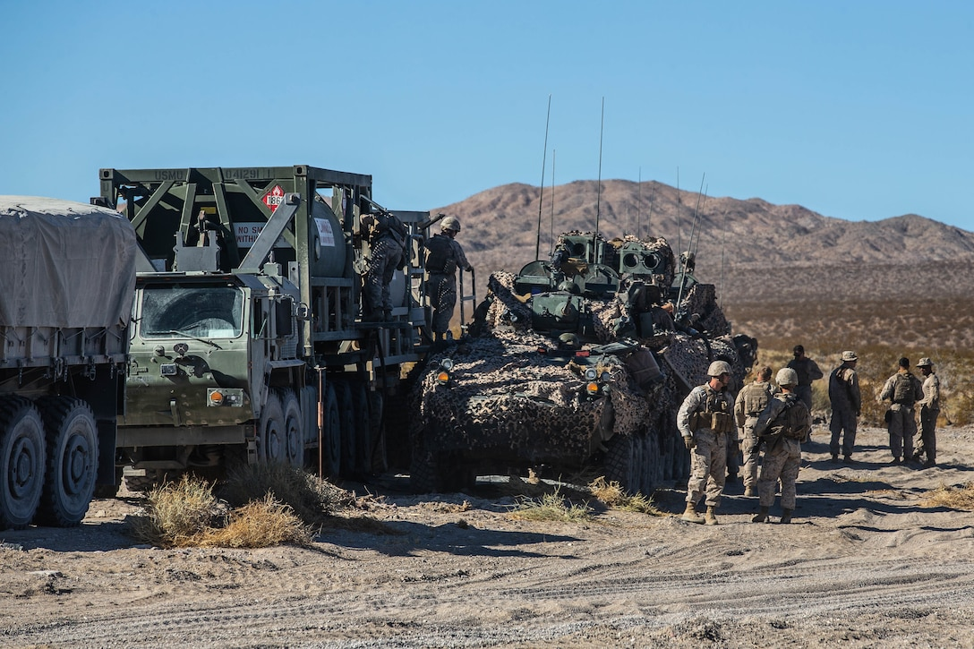 Marines stand near some equipment in the desert.