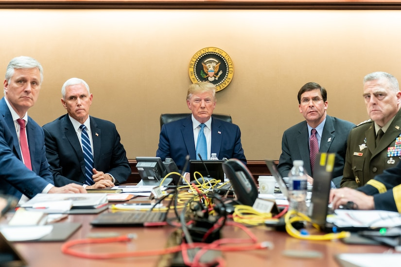 The president and vice president watch a monitor in the White House situation room with military and civilian advisors.