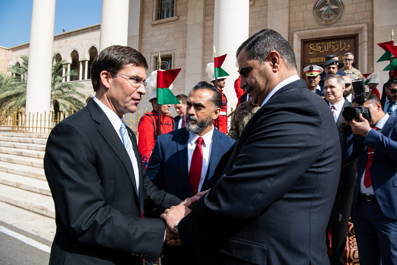 Two men shake hands as a third man looks on outside government building.