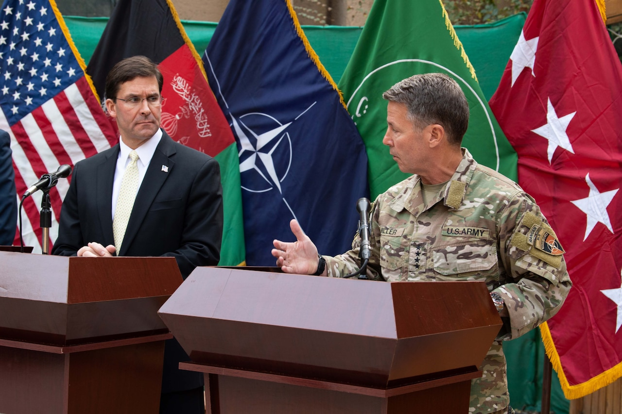 A man in civilian clothing and a man an Army uniform stand behind podiums with flags in the background.