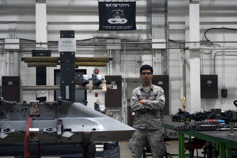 Senior Airman Jordan Harrison, 51st Munitions Squadron F-16 armament systems technician, poses under a weapons banner Oct. 23, 2019, at Osan Air Base, Republic of Korea. (U.S. Air Force photo by Staff Sgt. Gregory Nash)