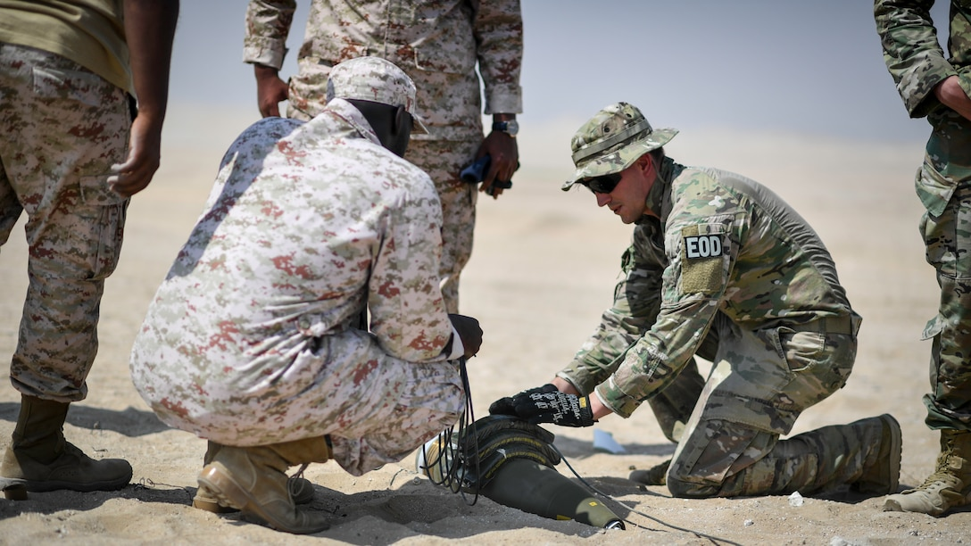 U.S. Army Sgt. 1st Class Jesse Harris, 744th Ordnance Company operations sergeant, places C-4 high explosives on to a 155MM insensitive high explosive round before a munitions disposal training at the Udari Range, Kuwait, Sept. 30, 2019. C-4's high cutting ability when detonated makes it the ideal explosive to use in the disposal or controlled detonations of insensitive high explosive rounds.