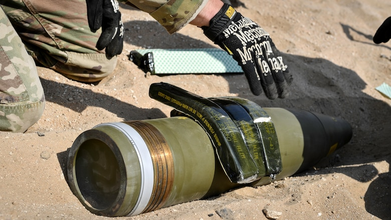 U.S. Army Sgt. 1st Class Jesse Harris, 744th Ordnance Company operations sergeant, places C-4 high explosives on to a 155MM insensitive high explosive round before a munitions disposal training at the Udari Range, Kuwait, Sept. 30, 2019. C-4's high cutting ability when detonated makes it the ideal explosive to use in disposal or controlled detonations of insensitive high explosive rounds.
