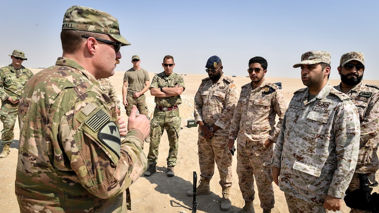 U.S. Army 1st Sgt. Adam Blunkall, 744th Ordnance Company first sergeant, speaks with Kuwaiti Ministry of Defense EOD technicians before an insensitive munitions disposal training at the Udari Range, Kuwait, Sept. 30, 2019. The training was designed for U.S. and Kuwaiti forces to share techniques, synchronize capabilities and build partnerships.