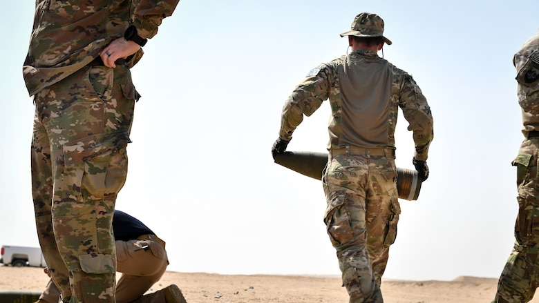 U.S. Army Sgt. 1st Class Jesse Harris, 744th Ordnance Company operations sergeant, carries a 155MM insensitive high explosive round before a munitions disposal training at the Udari Range, Kuwait, Sept. 30, 2019. The training was designed to demonstrate proper insensitive munitions disposal by using C-4 high explosives to properly detonate and consume the 155MM artillery round.