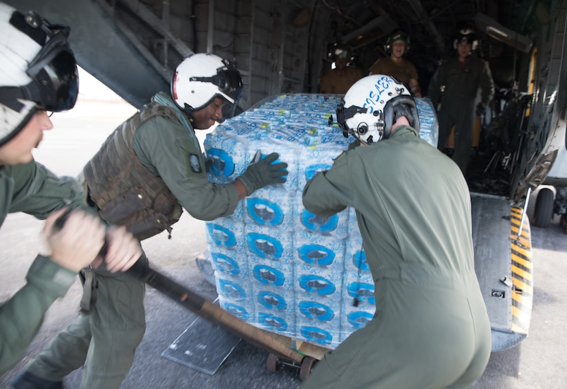 Service members remove a pallet of water from the back of an aircraft.