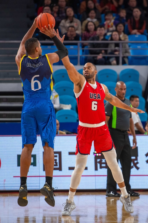 Blue-clad basketball player puts up a jump shot as red-clad opponent tries to block it.