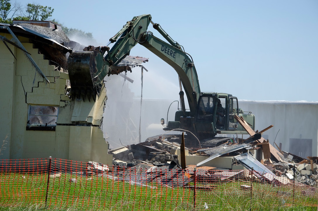 A Georgia Army National Guard Soldier with the 877th Engineer Company, 878th Engineer Battalion, operates an excavator to demolish a building scheduled for demolition at  Fort Benning.