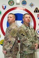 From left to right - Master Sgt. Joseph Howard, S-3 (operations) noncommissioned officer in charge (NCOIC), 450th Movement Control Battalion (MCB), and Master Sgt. Bryant Howard, Trans-Arabian Network (TAN) NCOIC, 450th MCB, stand back to back at Camp Arifjan, Kuwait, Oct. 24, 2019. This is Joseph and Bryant's third time being deployed together - being deployed together twice to Iraq in 2003 and 2009. (U.S. Army Reserve photo by Spc. Dakota Vanidestine)